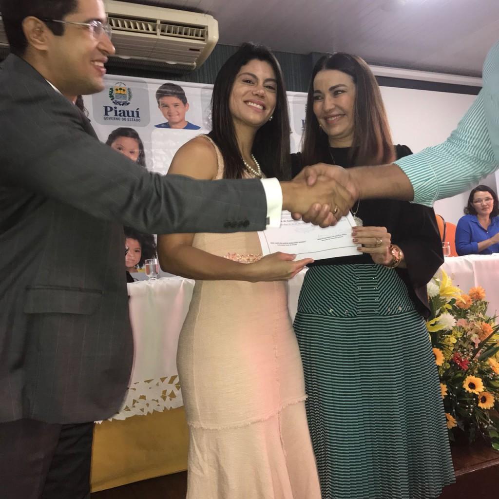 Q Coordenadora de  Licitação, Prhiscilla de Queiroz, no momento em que recebeu o certificado de participação no curso