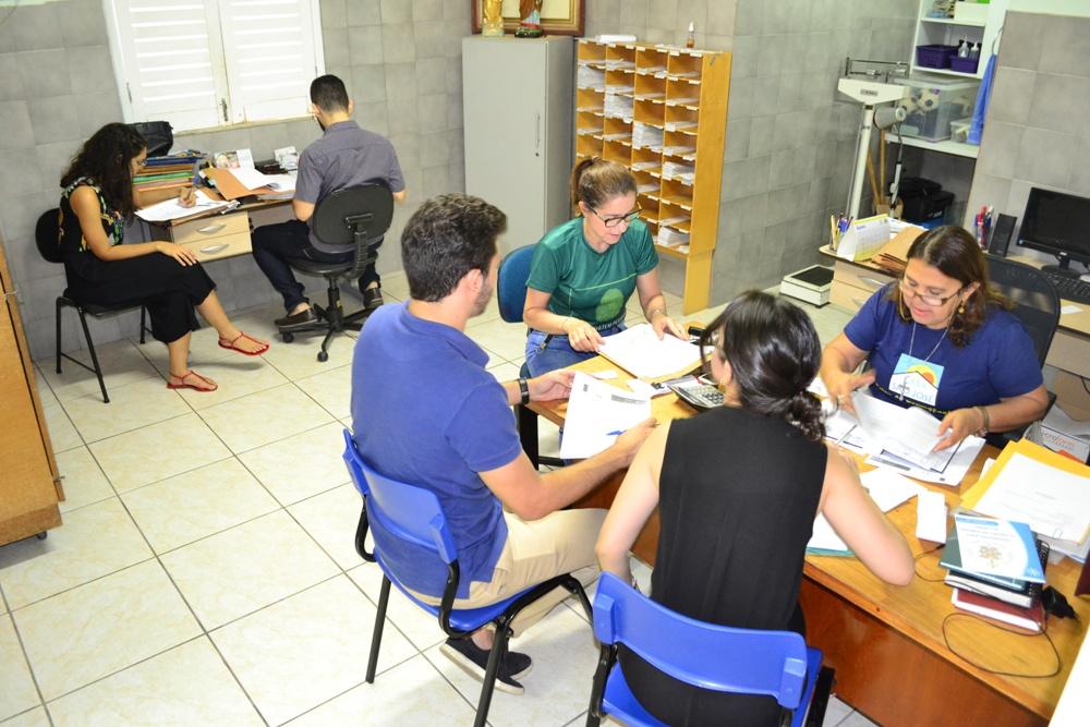 Equipe da Defensoria e Coordenadora da Casa examinam fichas dos idosos